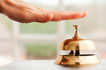 Hand ringing brass bell on hotel reception desk